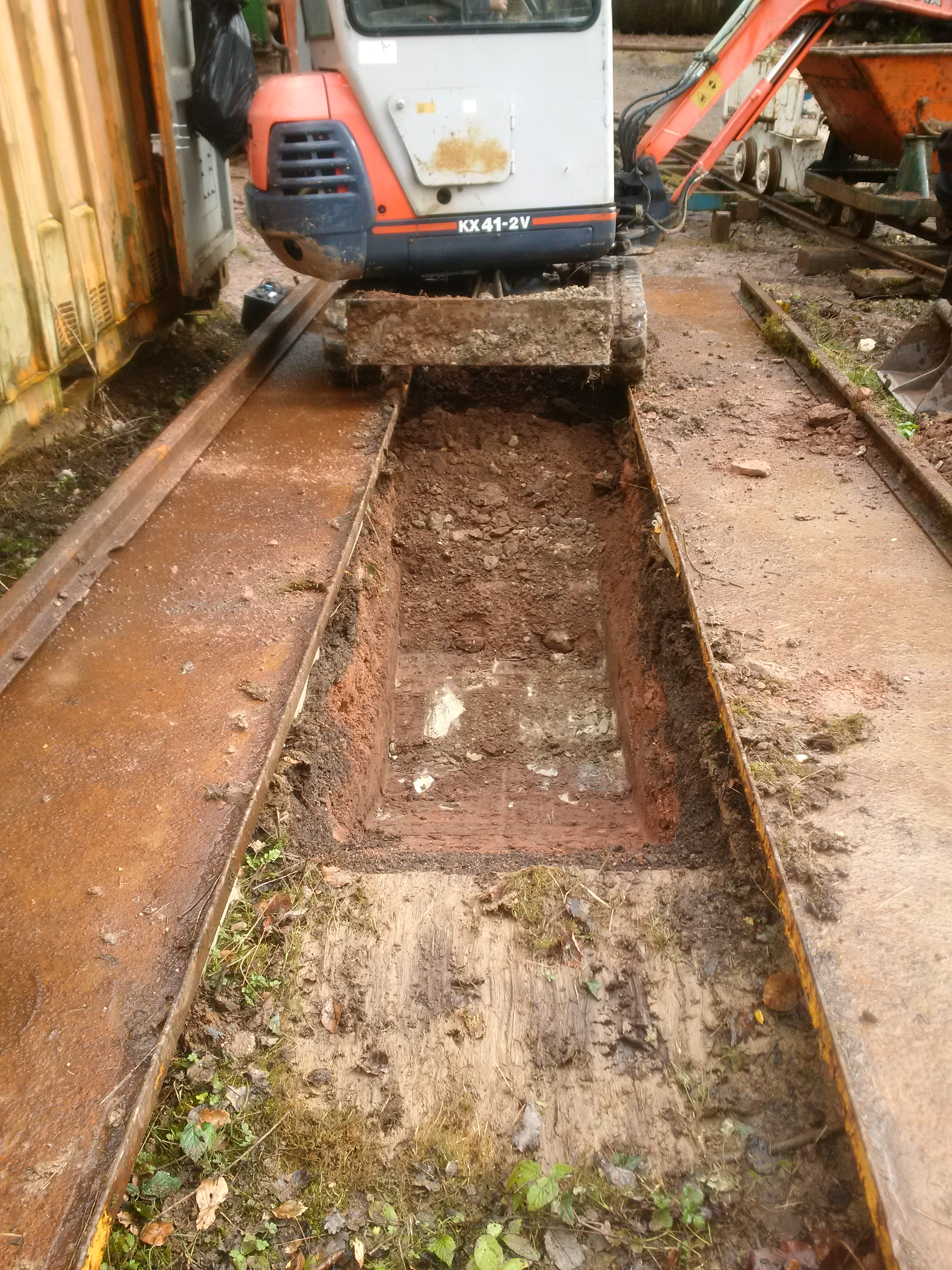 Mini digger creating an inspection pit